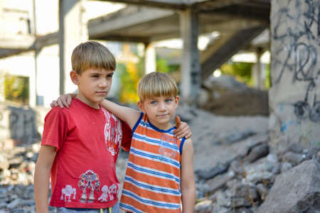 Two brothers are standing in an embrace against the backdrop of an unfinished and abandoned building, a concept of the life of street children of orphans. Imagens