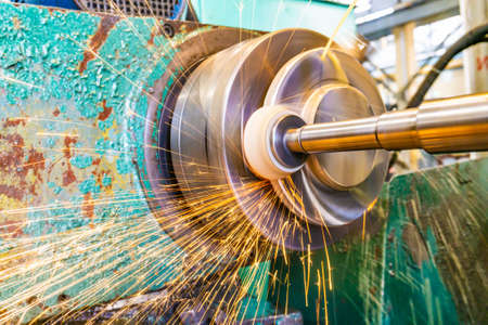 Grinding metal, abrasive wheel at high speeds removes part of the metal on the machined surface of a round part.