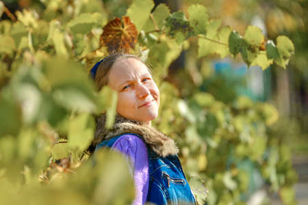 Portrait of a girl among grape leaves on a bright autumn day.