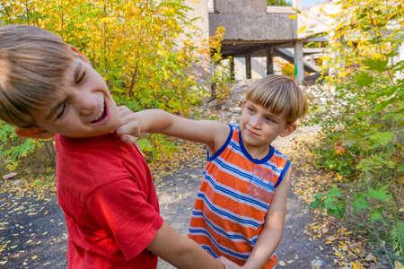 Dwóch chłopców kłóci się, jeden uderza drugiego pięścią w twarz.
