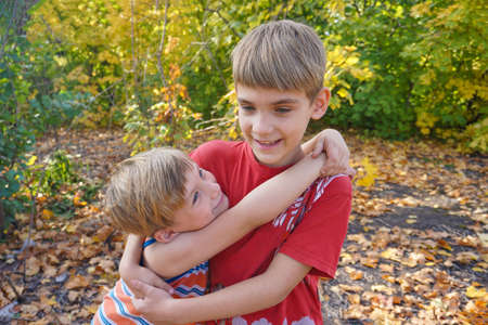 The younger brother hugs the older one and looks at him, two loving brothers are standing in an embrace in the park against the background of autumn leaves.