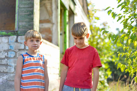 Two brothers are standing near a burned-out house, who lost their homes as a result of hostilities and natural disasters.