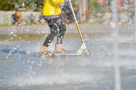 A girl in a yellow jacket riding a scooter in a fountain under spray of water.