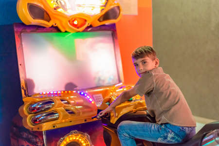 A boy on children's rides in a shopping center.