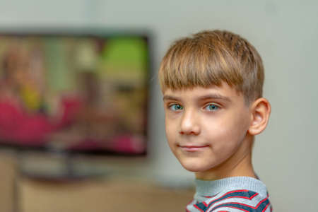 The boy looks at the camera on the background of the TV in the rest room. Stockfoto