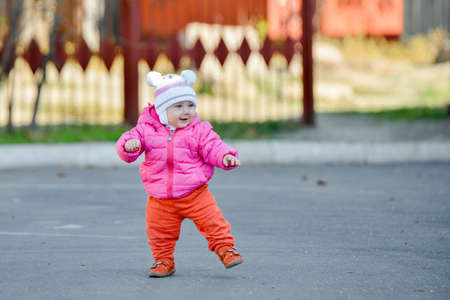 A little girl in a red jacket learns to walk on the road in the fall afternoon. 스톡 콘텐츠