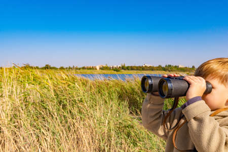 A boy with binoculars in the reeds is watching the wildlife.