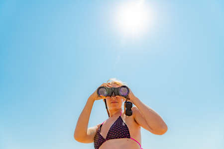 A girl in a swimsuit looks through binoculars at the camera on a background of elephant sky.