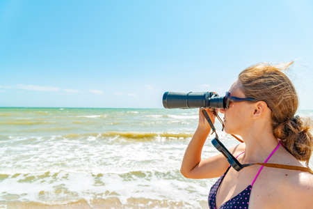 A girl in a swimsuit looks through binoculars at the sea on the beach. Reklamní fotografie