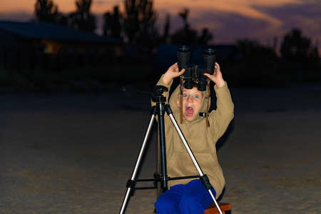A surprised boy with an open mouth saw something with binoculars. Reklamní fotografie