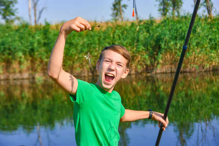 A fishing boy is trying to eat a caught fish for fishing rod.