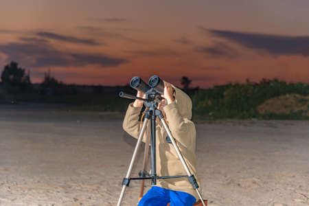 A boy looks through binoculars on a tripod against the background of an evening sunset.