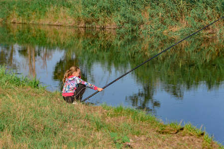 A girl with a long fishing rod sits on the riverbank awaiting a catch.