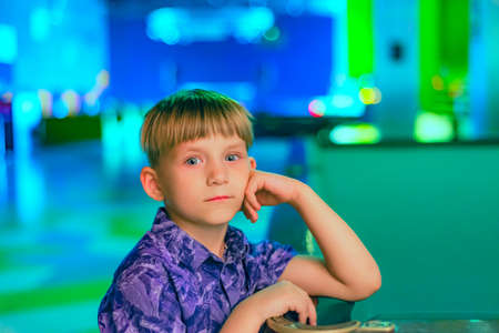 A pensive boy stands near the pool table, supporting his head with his hand. Reklamní fotografie