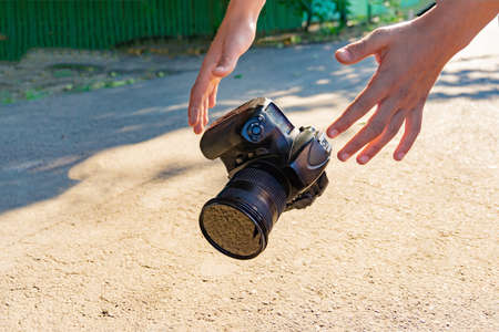 The camera falls on the asphalt, and a person tries to catch it with his hands. Reklamní fotografie