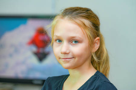 A young and beautiful girl on the background of tv looks at the camera. Reklamní fotografie