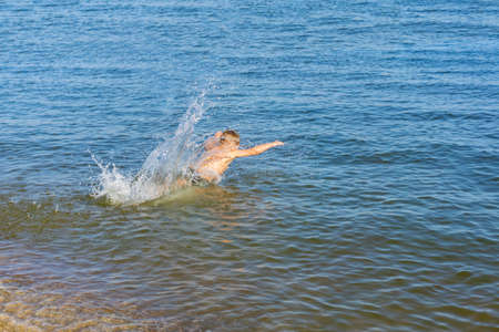 A man dives in sea water, splashes from the water fly in different directions.