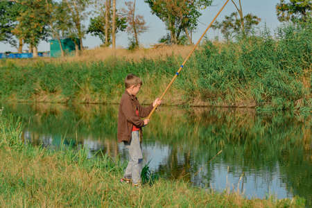 A boy holds a fishing rod over the water for fishing.