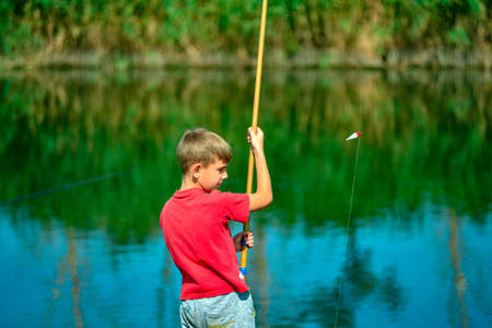 A boy in a red shirt throws a fishing rod on the catch river.