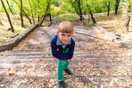 A boy stands on the old steps in the park, leaning on his knee and looking at the camera, wide-angle photo.