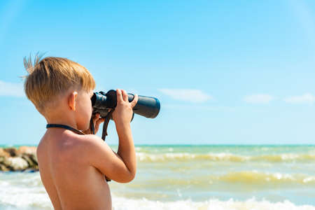 A boy with binoculars looks at the sea against a blue sky.