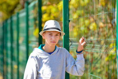 An angry and displeased guy in a hat holds on to a green fence and looks at the camera.