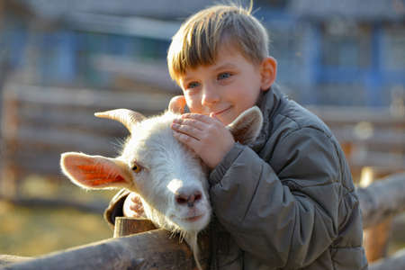Joyful and happy boy hugs and strokes a horned goat, the concept of the unity of nature and man. Reklamní fotografie
