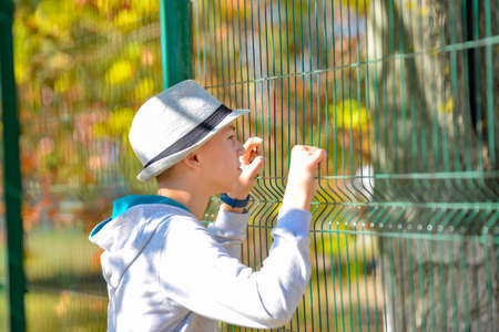 A guy in a gray hat holds on to a metal fence net and looks inside.