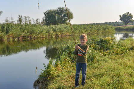 A joyful and happy boy rejoices at his first catch of fish on a fishing rod on the river.