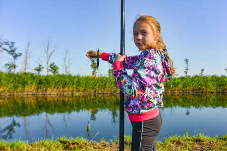 A girl with a fishing rod shows a caught fish.