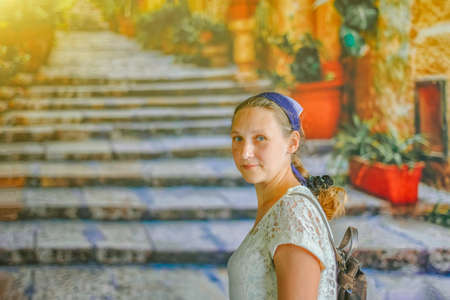 Portrait of a girl in the ancient city on the background of old steps.