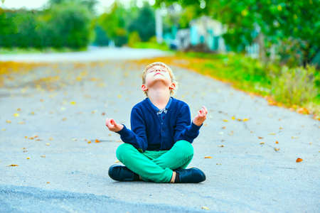 The boy sits on the street in a lotus position and meditates with his head raised to the sky.
