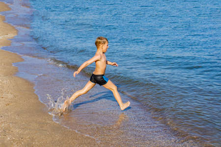 A boy runs into the water on the seashore.