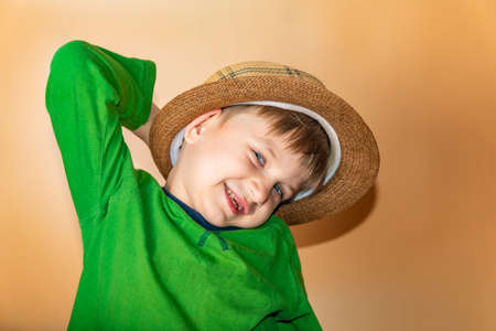 Joyful and happy boy in a straw hat and green clothes smiling and looking at the camera.