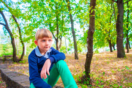 A young and cute boy in green jeans sits on a curb in a park with his hand on his knee.