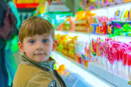 Surprised and joyful boy in a candy store.