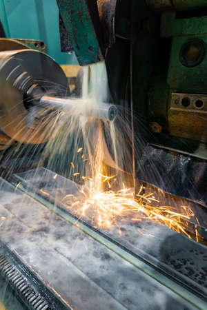 Grinding machine for metal processing with abrasive tools in production with cooling and sparks.