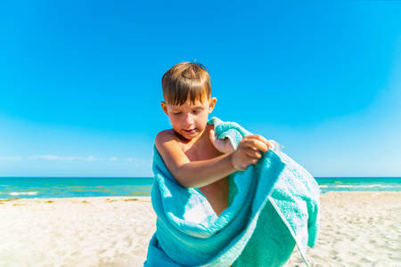 The boy on the beach hides with a towel and wipes himself from sea water after swimming in the sea.