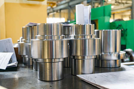 Parts after turning and milling on the machine against the background of a technical drawing. Stock Photo