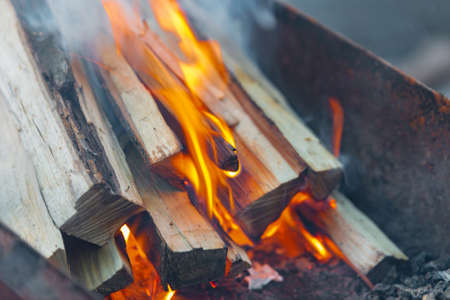 Burning logs for kindling a fire, flame and smoke on fire. Logs in a barbecue for frying meat.