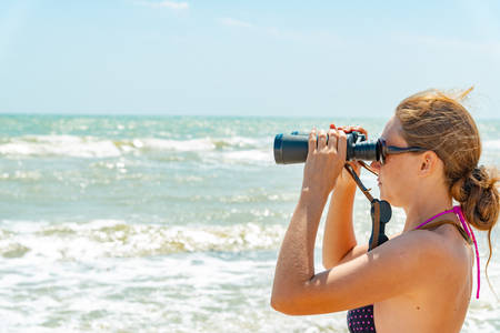 A girl in a swimsuit looks through binoculars at the sea on the beach.