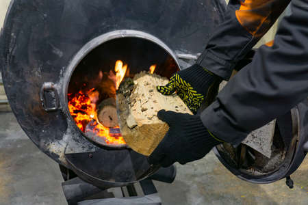 A worker throws firewood into an oven to heat a room. Imagens