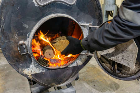 A worker throws firewood into an oven to heat a room. Banque d'images - 138093483