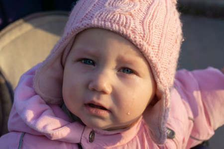 A little girl with tears crying in a pram.