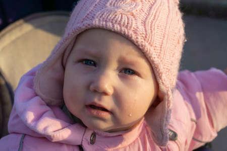 Une petite fille pleurant en larmes dans un landau.