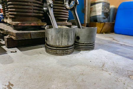 Piston with connecting rod next to internal combustion engine disassembled Фото со стока