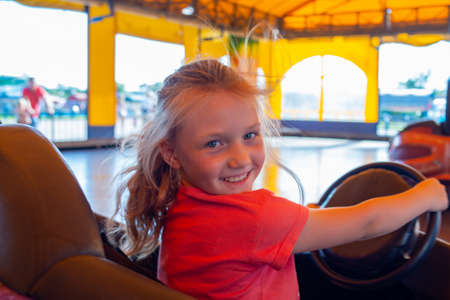 The girl rides electric cars in the amusement park, tired but joyful, looking into the camera Stock Photo