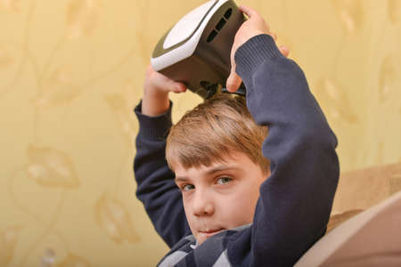 A child removes VR glasses after watching a 3D video.