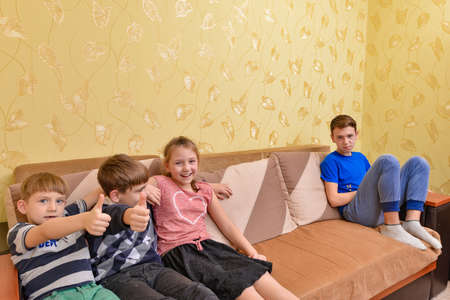 The offended teenager does not want to talk with anyone and sits separately from his brothers and sisters. Stock Photo