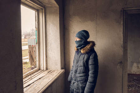 A teenager looks out the window in an abandoned and ruined house Foto de archivo